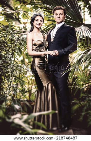 Gorgeous lady in long evening dress and with tiara on a head and handsome man in classic suit  - stock photo