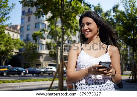 Gorgeous Latin woman with mobile phone in hands smiling to someone while standing on a street in summer day, young happy female waiting for call on cell telephone during strolling in unfamiliar city  - stock photo