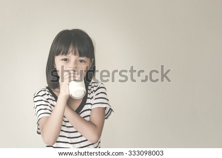 Gorgeous little girl wearing striped encouraged to drink milk - Vintage Filter Effect - stock photo