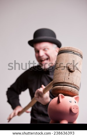 gorgeous madcap  smashes money with a big wooden  sledgehammer - stock photo