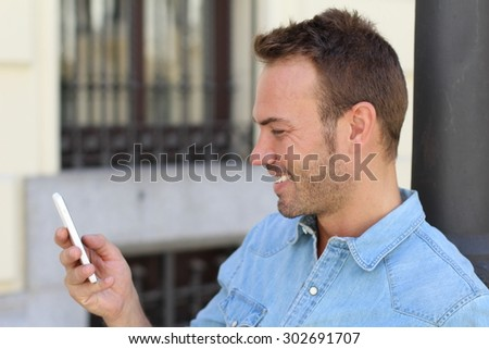 Gorgeous man spending time in his city. Confident young man holding mobile phone outdoors - stock photo
