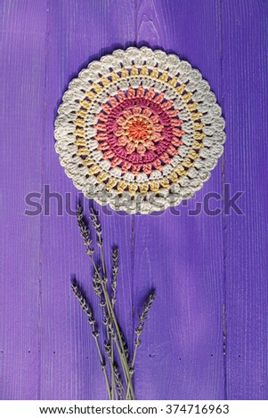 Gorgeous Mandala Crochet Doily and Lavender Flowers  on Purple Rustic Wooden Background - stock photo