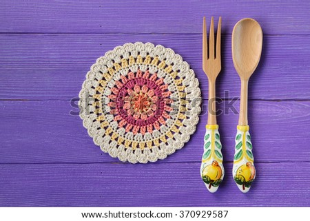 Gorgeous Mandala Crochet Doily and spoon with fork for salads on Purple Rustic Wooden Background - stock photo