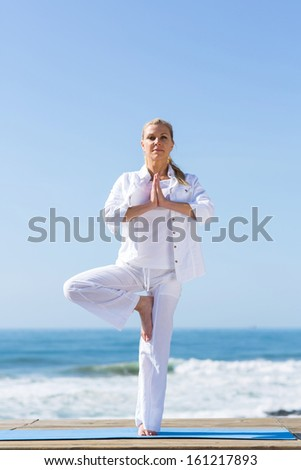 gorgeous middle age woman doing yoga exercise at the beach - stock photo