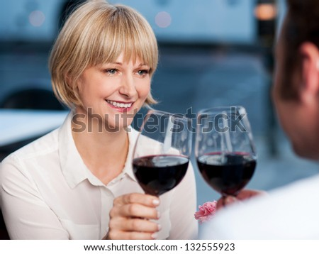 Gorgeous middle aged woman looking at her man with love and toasting wine. - stock photo