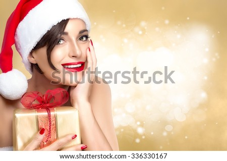 Gorgeous Miss Santa in a festive red hat with a golden Christmas gift clutched to her chest holding her hand to cheek smiling at the camera, over golden glitter defocused background with copy space - stock photo