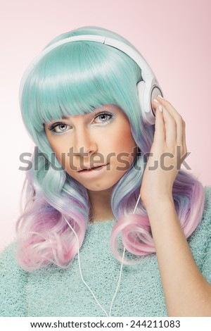 Gorgeous modern teenage girl with headphones. Beautiful trendy young woman with pastel green and pink hair and bright makeup listening to music against pink background. - stock photo