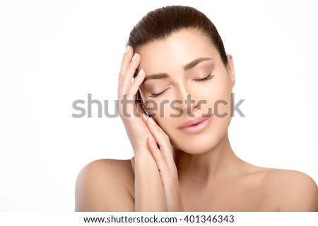 Gorgeous natural young woman with a smooth complexion and bare shoulders with hands raised gracefully to her cheek posing with eyes closed in a head and shoulders beauty portrait isolated on white.  - stock photo