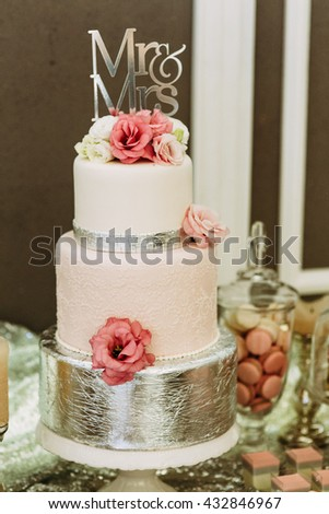 Gorgeous pink wedding cake with flowers - stock photo
