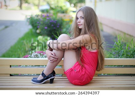 Gorgeous pretty girl sitting in a pink dress - stock photo