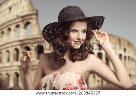 Gorgeous, pretty, happy woman in summer hat and top with flowers pattern. She has got curly hairstyle and nice lolorfum makeup. - stock photo