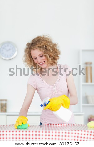 Gorgeous red-haired woman cleaning a cutting board in the kitchen in her apartment - stock photo
