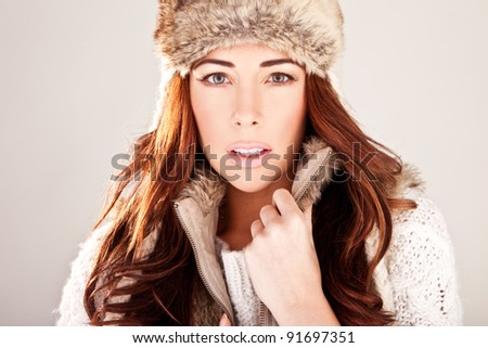Gorgeous Redhead Fashion Model In Winter Fur close-up studio head-shot looking directly at camera - stock photo