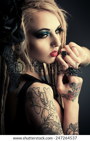 Gorgeous sexy girl with black make-up and long dreadlocks. Gothic style. Fashion. Cosmetics, hairstyle. Tattoo. - stock photo