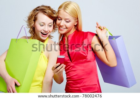 Gorgeous shoppers reading sms on mobile phone - stock photo