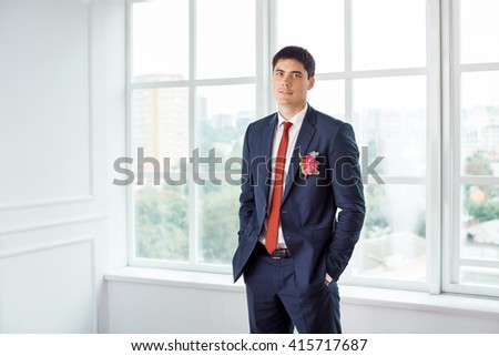 Gorgeous smiling groom looking at camera. Handsome man in a suite with a buttonhole standing against a window indoors - stock photo
