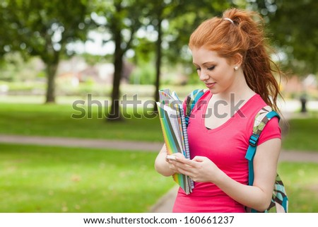 Gorgeous smiling student holding notebooks texting on campus at college - stock photo