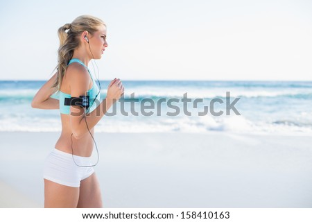 Gorgeous sporty blonde in sportswear jogging on a sunny beach - stock photo