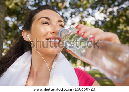 Gorgeous sporty woman drinking water out of a bottle while listening to music - stock photo