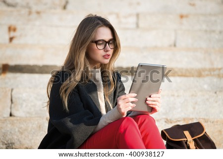 Gorgeous student girl sitting on stair wearing eyeglasses and reading book on tablet - stock photo