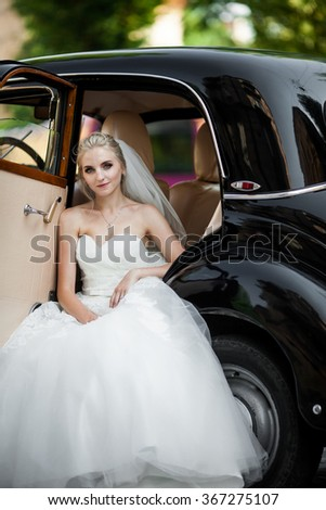 Gorgeous stylish blonde bride posing in retro black car in white dress - stock photo