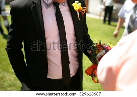 gorgeous stylish elegant groom and best man holding colorful bouquets - stock photo