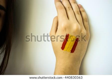 Gorgeous stylish girl football fan with spanish flag on face closeup - stock photo