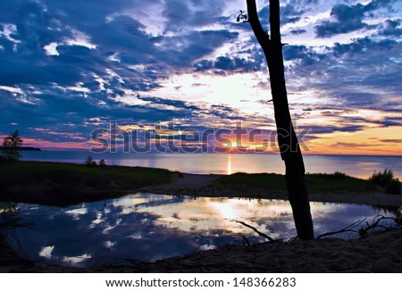 Gorgeous sunset over Lake Huron with sunset sky perfectly mirrored on the river in the foreground. Port Crescent State Park. Port Austin, Michigan. - stock photo