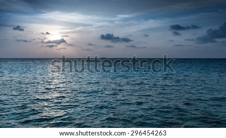 Gorgeous sunset over the ocean. Rays through the clouds painted in bright  colors. - stock photo
