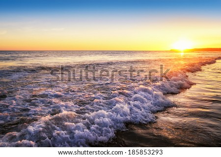 Gorgeous tranquil sunset at the beach with clear sky and emotionally appealing colors - stock photo