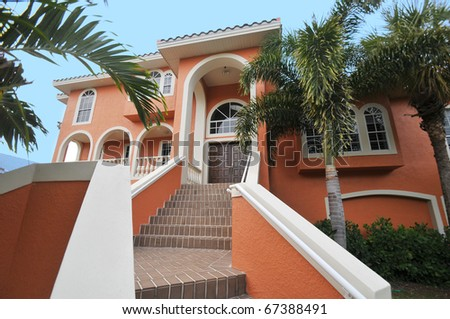 Gorgeous two-tiered stairway leading up to a magnificent Florida mansion. - stock photo