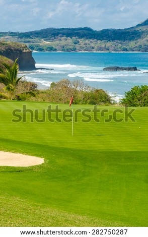 Gorgeous view at the beautiful golf course with sand bunkers at the ocean side. Vertical. - stock photo