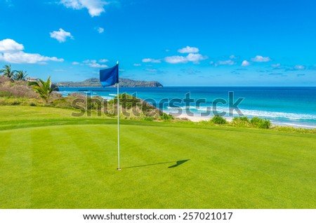 Gorgeous view at the golf course with blue flag at the ocean side. - stock photo