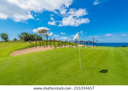 Gorgeous view at the golf course with white flag at the sand bunkers at the ocean side. Luxury Mexican resort. - stock photo