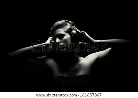 gorgeous woman in black and white tense light listening to music - stock photo