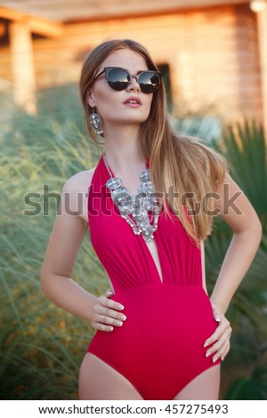 Gorgeous woman in sunglasses and elegant red bikini relaxing on jungle - stock photo