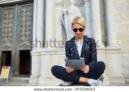 Gorgeous woman is reading information in website via touch pad,while is sitting against old architectural building. Young hipster girl is watching video what she took now on digital tablet during tour - stock photo