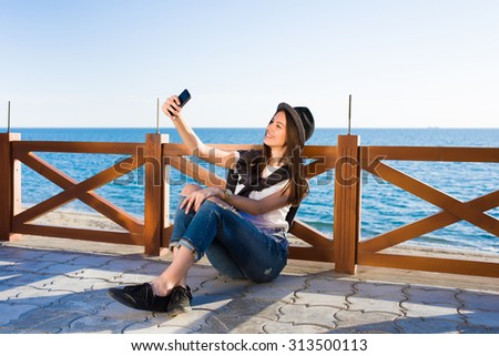 Gorgeous woman making self portrait with cell phone digital camera while enjoying sunny day during promenade, happy female hipster taking picture of herself on smart phone strolling on the beach - stock photo
