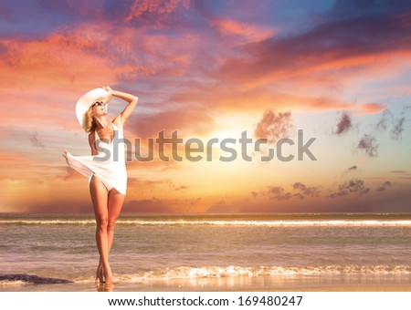 Gorgeous woman on the beach at sunset - stock photo
