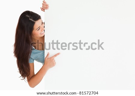 Gorgeous woman pointing at a board while standing against a white background - stock photo