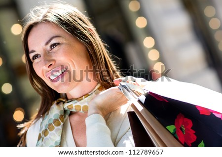 Gorgeous woman shopping outdoors and holding bags - stock photo
