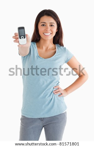 Gorgeous woman showing her mobile phone while standing against a white background - stock photo