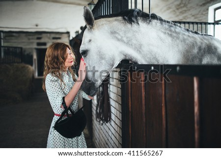 gorgeous woman stroking a beautiful gray horse - stock photo