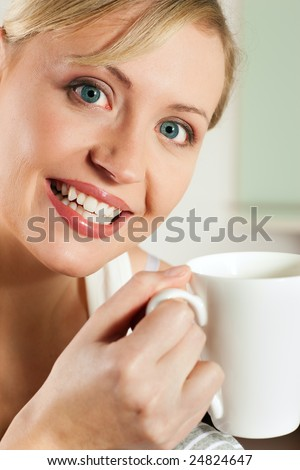 Gorgeous woman visibly enjoying a hot cup of coffee for breakfast - stock photo
