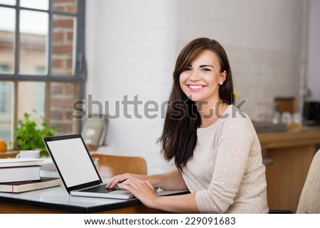Gorgeous woman with a happy beaming smile sitting at a table working at a laptop computer in front of a window - stock photo