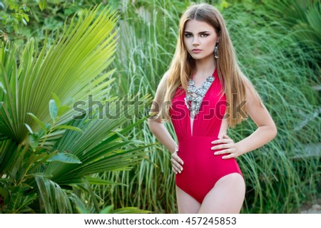 Gorgeous woman with dark hair in elegant  red bikini relaxing on jungle - stock photo