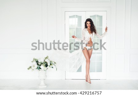 gorgeous woman with dark long hair posing indoor, wearing white lingerie,art, filters, noise added, concept, collage, dirty, fine film noise added - stock photo