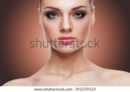 Gorgeous woman with perfect skin and make up on brown background in studio photo. Beauty and naturality - stock photo