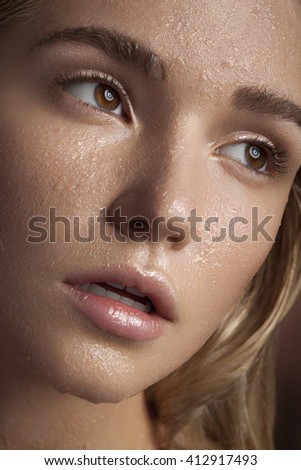 Gorgeous woman with perfect skin and water drops on face in close up photo. Beauty and health. Studio photo - stock photo