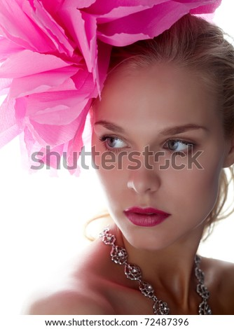 Gorgeous woman with pink flower on head looking aside - stock photo